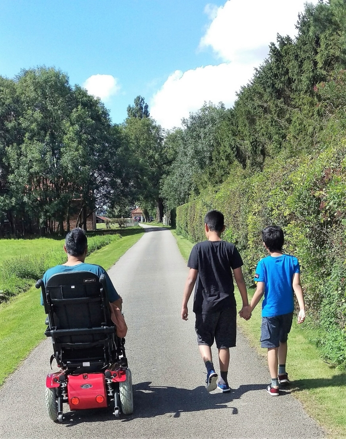 Family including father in a wheelchair and two sons walking along a paved path away from the camera. The sun is shining and there is green grass to the left handside and a green hedge on the right.