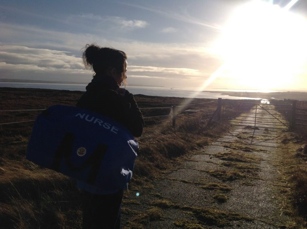 Image of a female nurse, side on looking towards the horizon. She carries a blue holdall marked nurse. Ahead of her is the sun, sea and rugged looking cliffs in the background. In the foreground is a rural track and a metal farm gate.