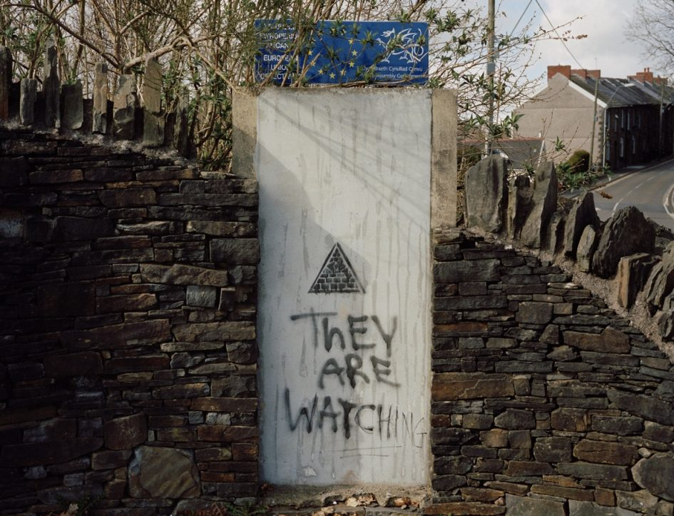 Picture of a traditional welsh stone wall. in the centre in a white panel with an EU star flag at the top. On the white panel is grafiteed the words They are watching